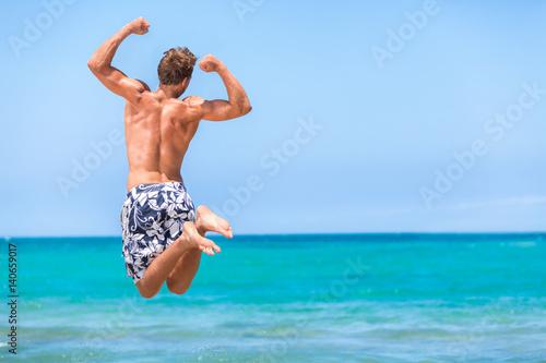 Fotografie, Tablou Happy fitness man jumping of goal achievement success on beach