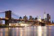 Brooklyn Bridge over East River in city against sky at dusk