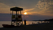 Silhouette of a lifegueard watchtower, boat and people on a beach at sunset, Sithonia, Greece