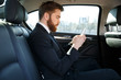 Side view of bearded business man using smartphone