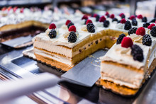 Slices Of A Layered Vanilla Cake With Cream Topped With Berries