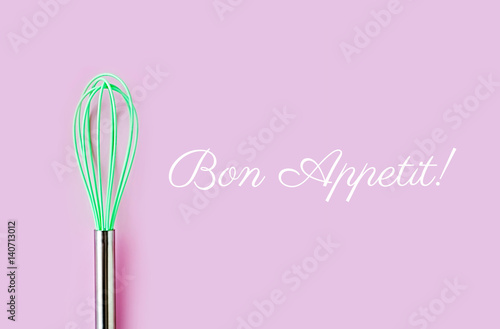 Fotografija  Neon green culinary whisk top view on colorful background