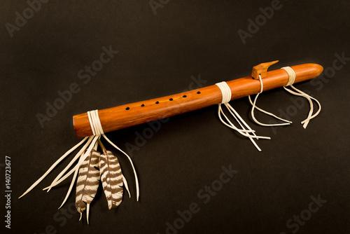 Plakat Primitive Antique Native American Flet z piórami na czarnym tle.