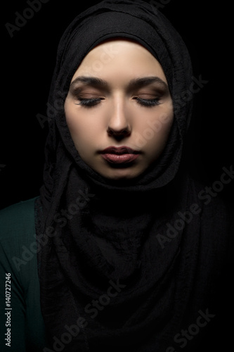 Fotografie, Obraz  Female wearing a black hijab as a conservative fashion choice to represent feminist freedom of expression and political statement