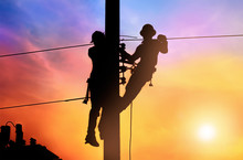 Silhouette Two Electrical Engineer On Electricity Pole, Work On Electric Post Power Pole And Repair Power Outage.