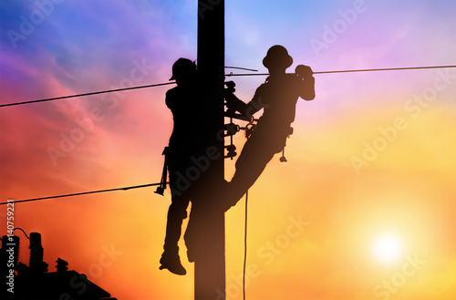 Fotografia Silhouette two electrical engineer on electricity pole, work on electric post power pole and repair power outage