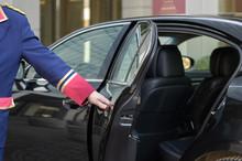 The Doorman Opens The Door Of A Luxury Car
