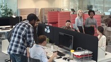Team Of Businesspeople Standing In Busy Office And Looking Over Shoulder Of Frustrated Male Colleague Working On Computer: They Discussing Problem And Trying To Find Solution