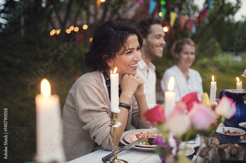 Smiling friends sitting at decorated table in garden party