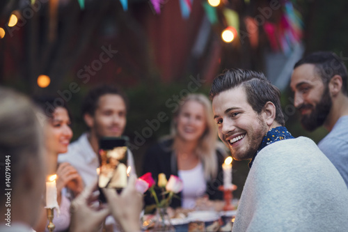 Woman photographing man while sitting with friends at garden party