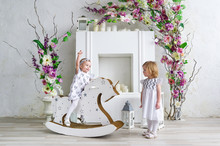Two Charming Little Girls Play In The Light Room Decorated With Flowers. Baby Girl Swinging On A Wooden Horse