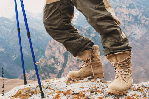 Close Up Of A Tourist S Foot In Trekking Boots With Sticks