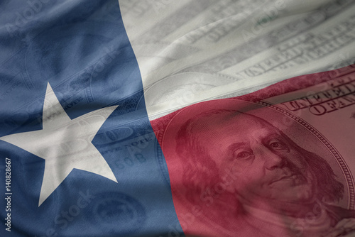 Poster Texas colorful waving flag of texas state on a american dollar money background. finance concept