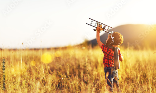Child pilot aviator with airplane dreams of traveling in summer  at sunset Canvas Print