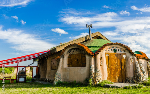 Cute colorful cartoon fairytale house against blue sky and clouds on a sunny day Wallpaper Mural