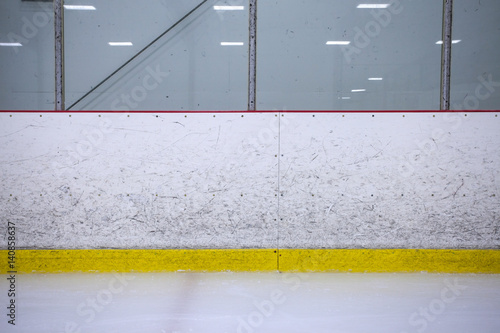 A straight on shot featuring well worn hockey boards in a recreational hockey rink.