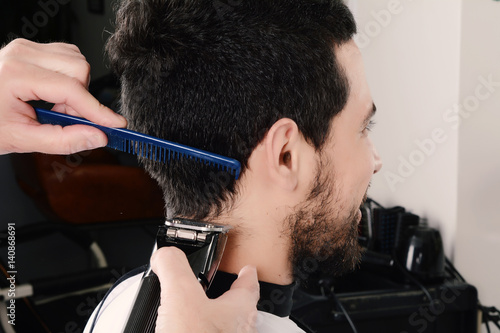Spoed Foto op Canvas Kapsalon Man having a haircut with hair clippers.