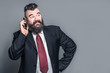 Adult bearded man in a suit talking on the phone
