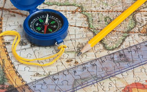 niebieski-kompas-linijka-i-zolty-olowek-lezace-na-mapie