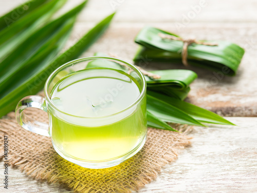 Glass of pandan juice and pandan leaves on wood background