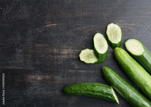 Cucumber and slices on dark wood background,top view