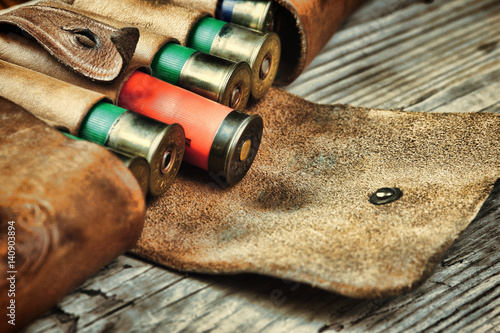 Poster Chasse Old hunting cartridges and bandoleer on a wooden table