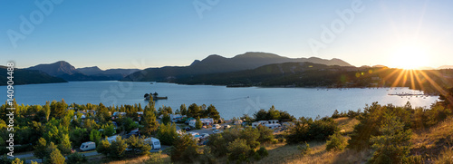 Tuinposter Kamperen Panoramic view of the lake Lac de Serre Poncon in the French Alps and a campsite with sunset