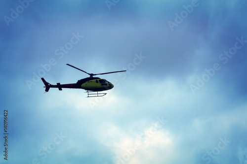 Tuinposter Helicopter Rotor helicopter flying against the blue sky background