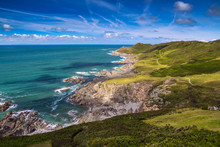 Picturesque View Of The North Coast Of Devon. Grunta Beach And Mortehoe Point In The Distance. Striped Sky. England