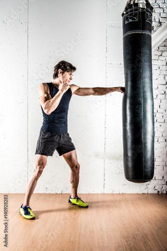 Kickboxer boxing in punching bag Canvas Print