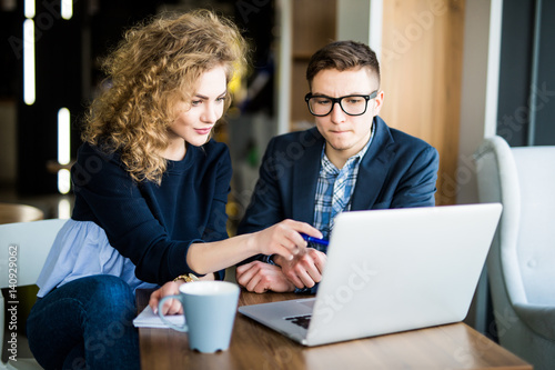Fotografía  Group of two coworkers working over laptop discuss in a modern office