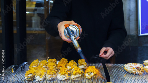Fotografie, Obraz  Sea food, Uni (Sea Urchin) grilled on the hot plate with the cooker at Tsukiji f