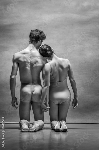 Couple of ballet dancers posing over gray background - 140930619