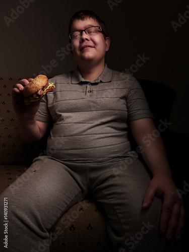 Photo Lonely fat guy eating hamburger. Bad eating habits.