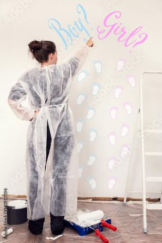 Junge Frau beim Streichen von Kinderzimmer, rosa oder blau ...