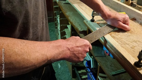 Midsection Of Carpenter Using Rasp At Workshop