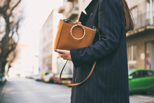 Detail Of A Fashionable Woman Wearing A Navy Blue Oversized Coat And A Brown Trendy Handbag. Perfect Spring Fashion Outfit.