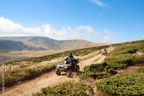 Tourists on quad bikes travel in the mountains. Carpathians