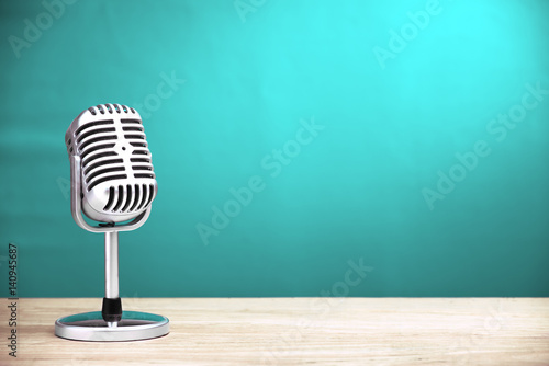 Photo Retro microphone on wooden table with turquoise wall background