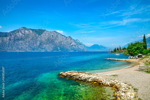 Carta da parati Summer embankment and beach landscape of Garda lake with high