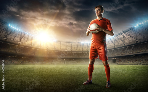 Obraz na plátně  soccer player in red uniform with a ball