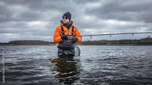 Cuadros en Lienzo Angler in Wathose mit Spinnroute watend nahe Küste mit Wald im kalten Wasser bei