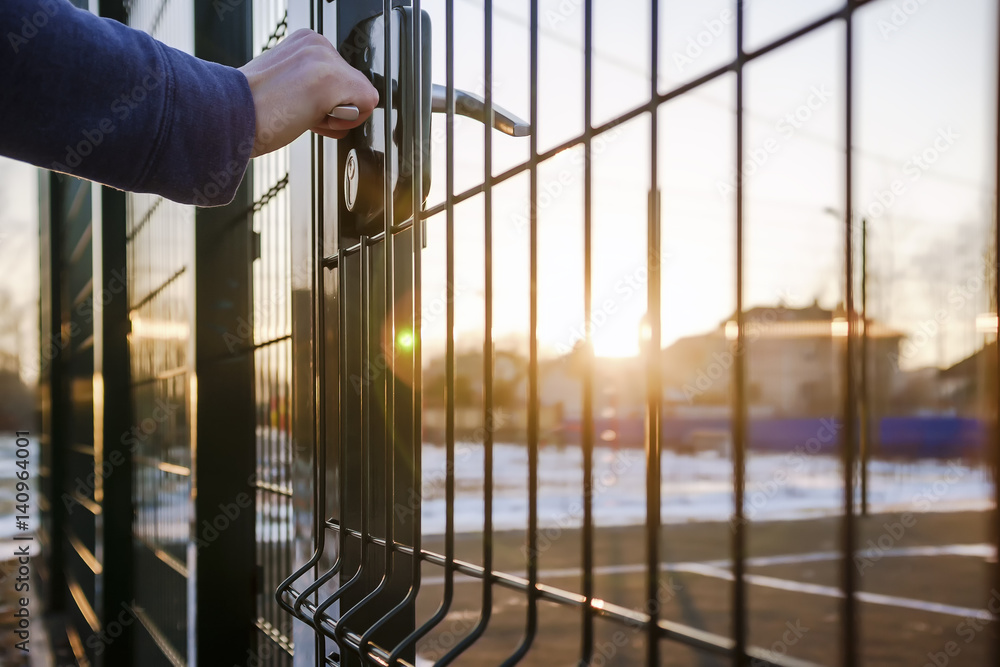 Fototapeta person wants get in on playground through the little gate of the welded wire mesh, wonderful winter sunny day