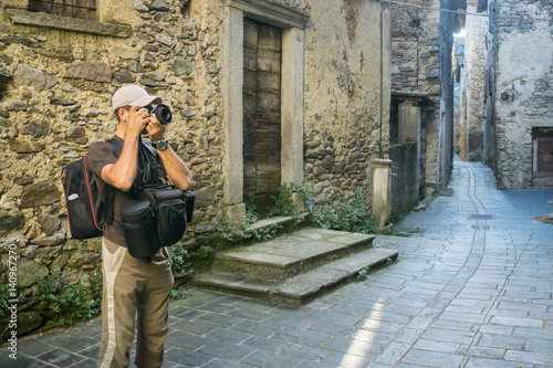 Photographer takes pictures of medieval old Italian town in summer