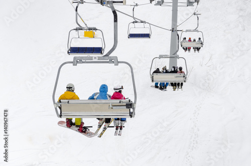 A chair lift transports skiers and snowboarders up a slope in a ski resort Tableau sur Toile