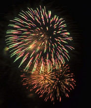 Red, Green, And Gold Fireworks Against A Black Sky