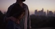Man lays arm around woman, slow motion sunset, LA cityscape in background