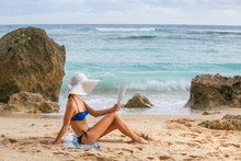 Young Woman Enjoying Time At The Beach, Reading Magazine