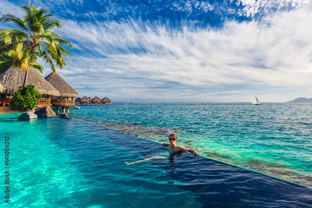Fototapeta Woman in the infinity pool in exotic island resort with bunalows over water