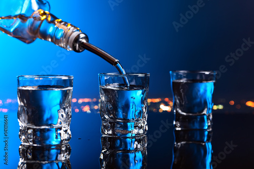 Photographie vodka in bar on a black  background